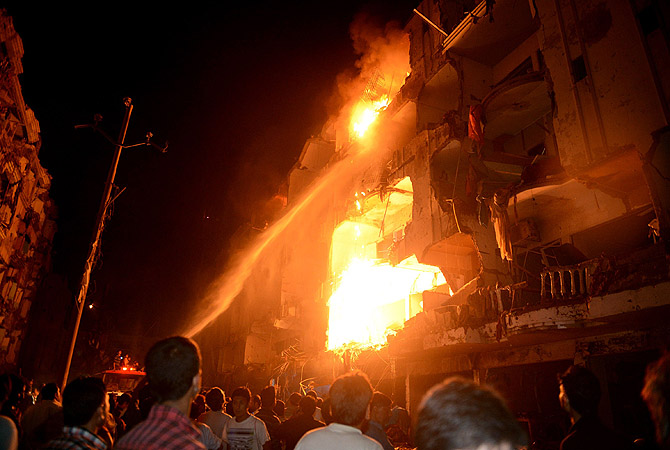 People gather as firefighters try to extinguish fire at the site of bomb blast in Karachi on March 3, 2013.?Photo by AFP