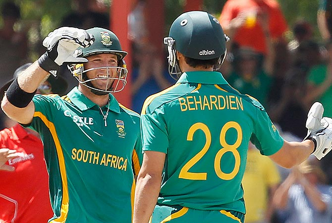 South Africa's Colin Ingram (L) celebrates his 100 runs with Farhaan Behardien. -Photo by Reuters