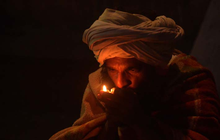 A Sadhu (Hindu holy man) smokes marijuana using a chillum, a traditional clay pipe, as a holy offering for Lord Shiva, the Hindu god of creation and destruction, near the Pashupatinath Temple on the eve of the Hindu festival Maha Shivaratri in Kathmandu.?Photo by AFP