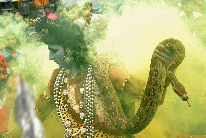 An Indian Hindu man dressed as Lord Shiva hold an 'ajgar' - snake - as he takes part in a religious procession on the eve of the Maha Shivratri festival in Jalandhar.?Photo by AFP