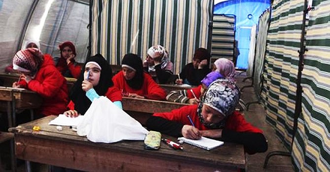 Syrian refugee girls attend class at the Bab Al-Salam refugee camp in Azaz. —Photo (File) Reuters