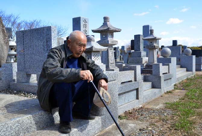 An elderly man sits as he and with his wife (not pictured) visit a cemetery to pay respects to their son who was killed in the March 2011 tsunami, in Minamisoma in Fukushima prefecture. March 11, 2013 marks the second anniversary of the 9.0 magnitude earthquake that sent a huge wall of water into the coast of the Tohoku region, splintering whole communities, ruining swathes of prime farmland and killing nearly 19,000 people.