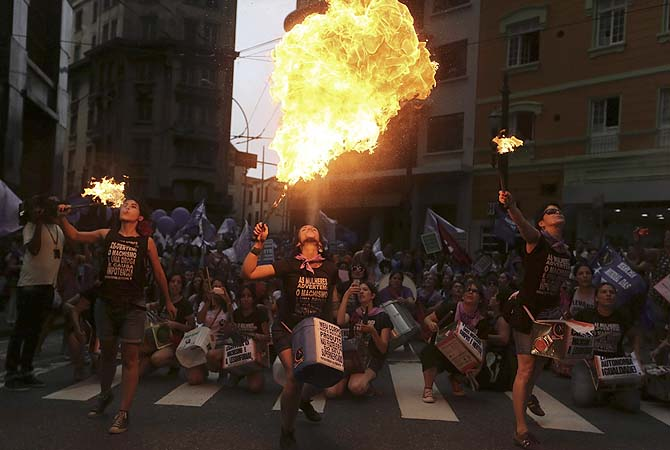 "Flamethrowers perform during a demonstration to commemorate International Women's Day in Sao Paulo March 8, 2013. The women's T-shirts read, ""Women warn: the male chauvinism is a drug and cause impotence"".?Photo by Reuters"