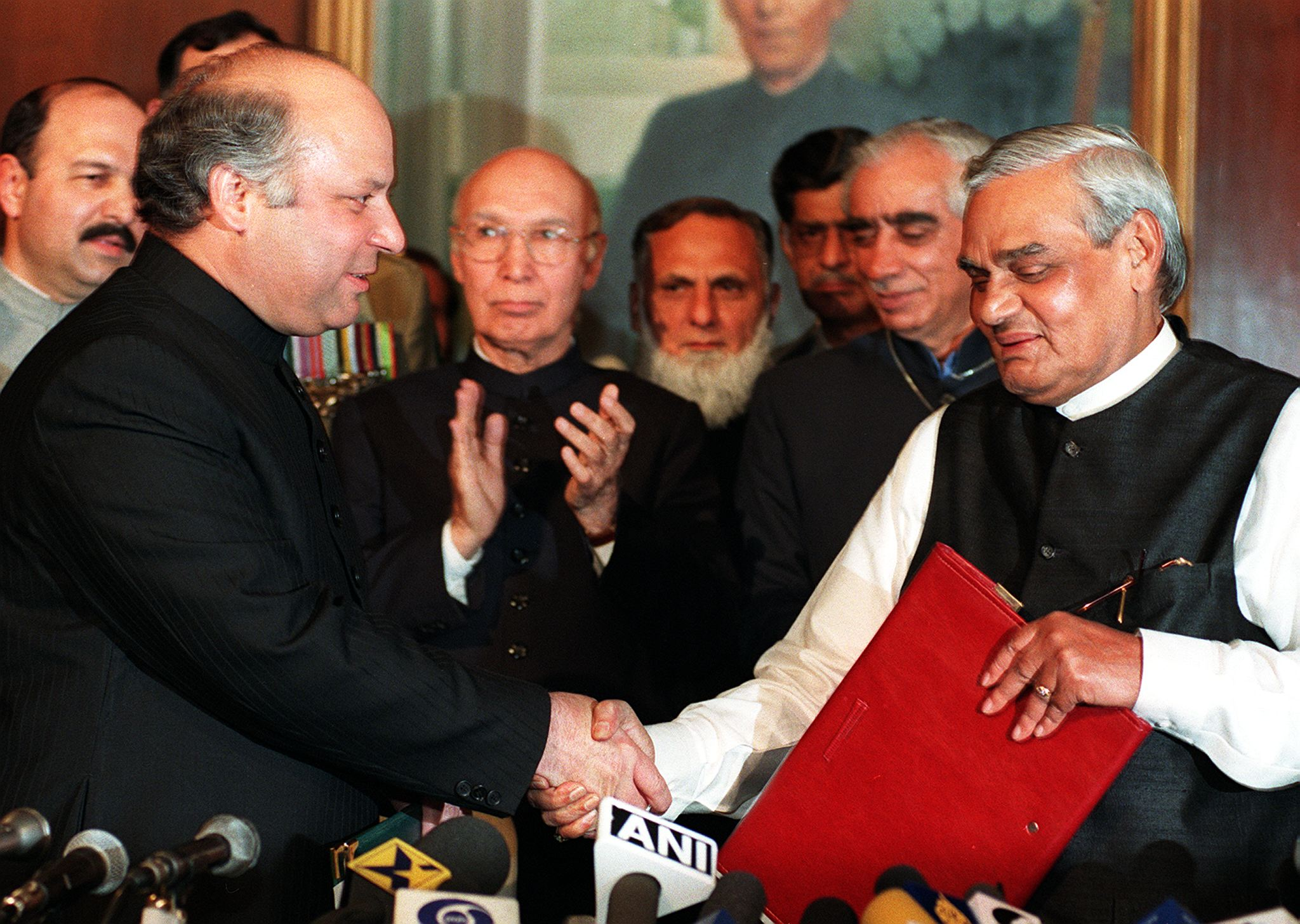 Prime Minister Nawaz Sharif (L) exchanges documents with his Indian counterpart Atal Behari Vajpayee (R) at Governor House in Lahore, 21 February.  Both leaders pledged to take immediate steps to reduce the risk of nuclear conflict and to intensify efforts to resolve all disputes, including the key issue of Kashmir. — Photo by AFP