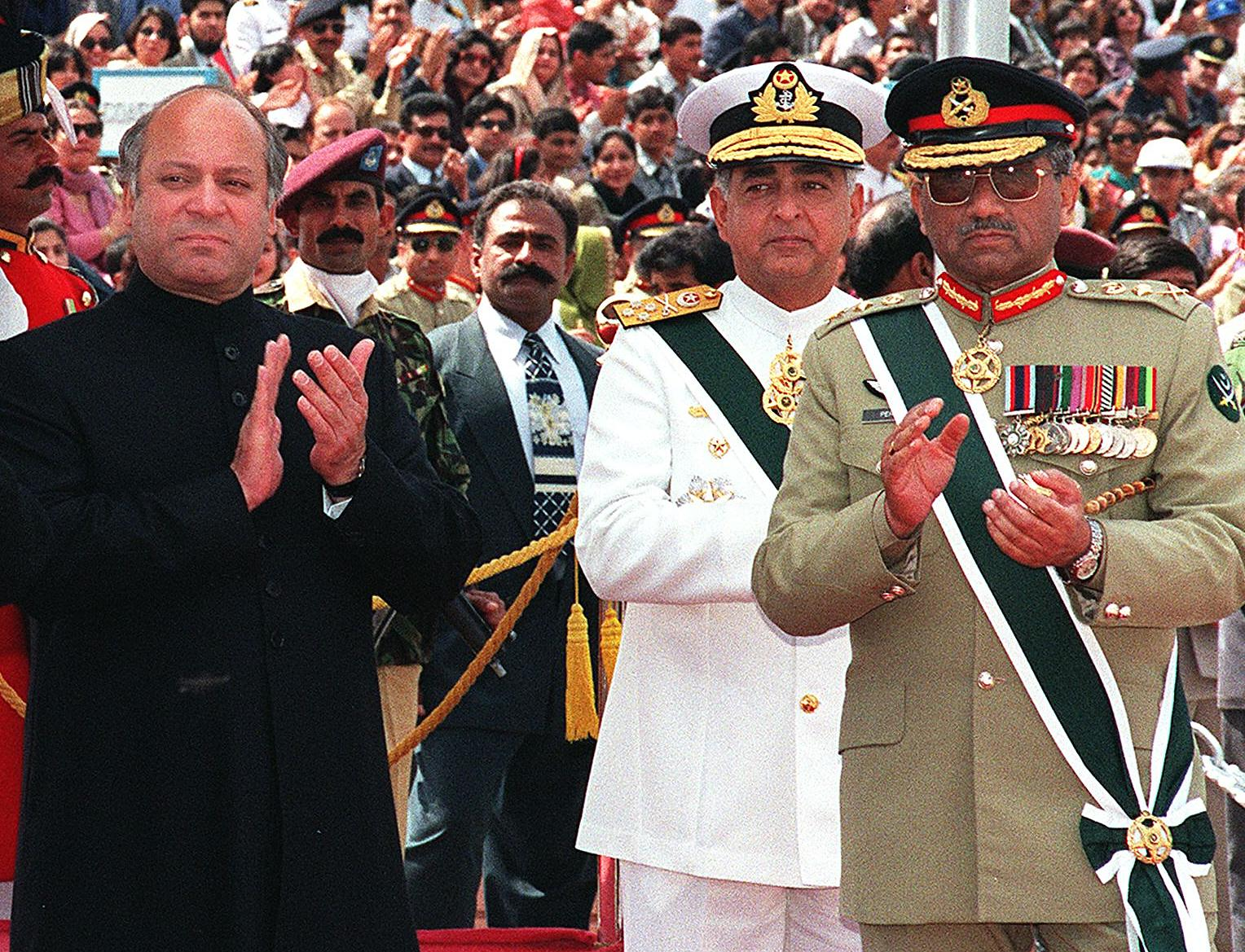 File photo shows Nawaz Sharif (L) with former army chief General Pervez Musharraf (R) applauding the performance of a military parade along with Naval Chief Admiral Fasiah Bokhari (C). Soldiers on 12 October disarmed police around Sharif's house and told him not to leave following the dismissal of General Musharraf earlier. — AFP