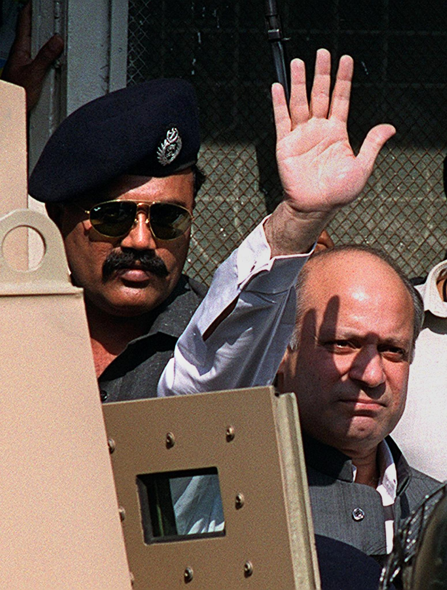 Toppled former prime minister Nawaz Sharif (R) waves at the media before appearing at Anti-Terrorism Court No 1 in Karachi, November 22, 1999.  Hundreds of police stood guard at the court where Sharif, who was to be questioned about accusations of treason, conspiracy to murder, kidnapping and hijacking a plane. — Photo by AFP/File