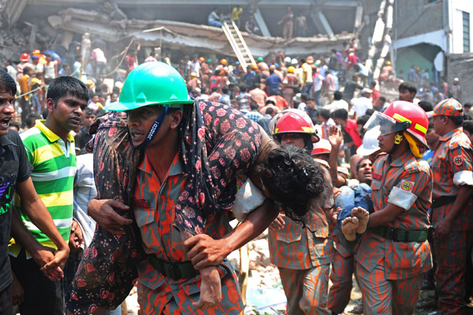 A Bangladeshi firefighter carries an injured garment worker to safety. —Photo by AFP