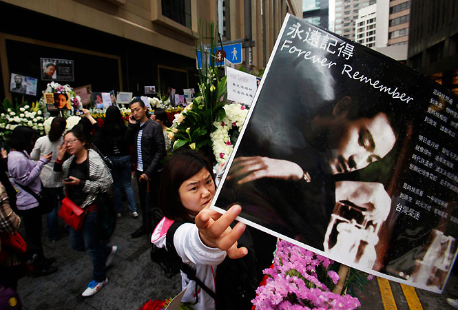 A fan adjusts a portrait of Leslie Cheung over a wreath outside the Mandarin Oriental Hotel.
