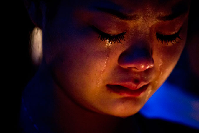 A fan of the late Hong Kong canto-pop star Leslie Cheung cries during a candlelight vigil.