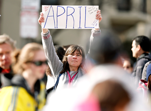 Justine Franco of Montpelier, Vt., holds up a sign near Copley Square in Boston looking for her missing friend, April, who was running in her first Boston Marathon.