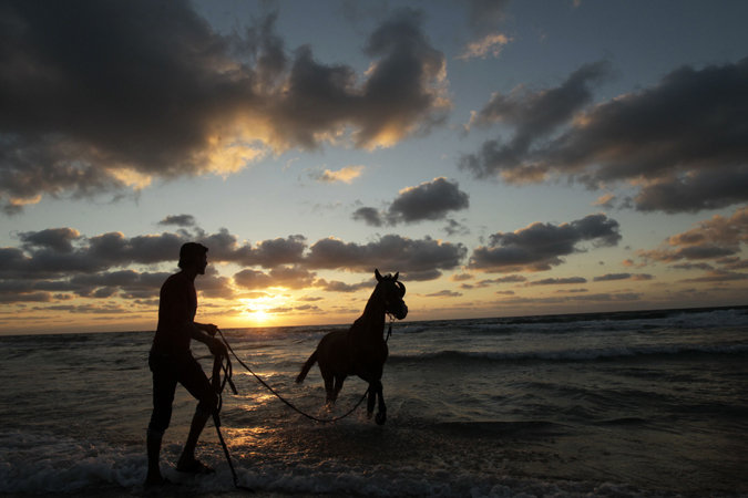 A Palestinian man walks with a horse along a beach as the sun sets in Gaza City on April 12, 2013.