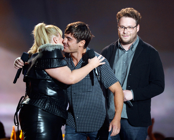 (L-R) Host Rebel Wilson, actors Zac Efron and Seth Rogen speak onstage during the 2013 MTV Movie Awards.