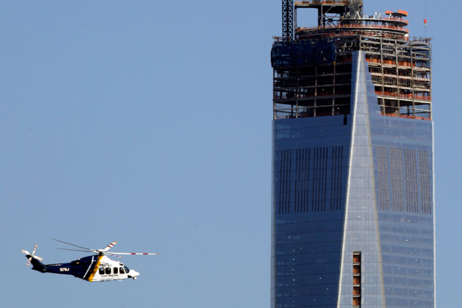 A New Jersey State Police helicopter flies by the construction site of One World Trade Center in Manhattan seen from The Heights neighborhood of Jersey City. New York is securing its city in the wake of explosions near the finish line at the Boston Marathon.