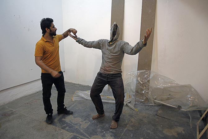 "Saud Baloach, 28, a fine art artist, shows his incomplete statue ""The Burden"" during an interview with Reuters at Government College University in Lahore."
