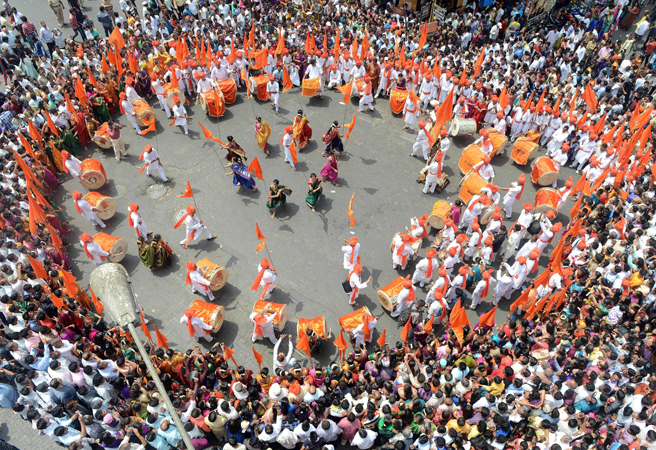 People crowd around a group of performers during a procession celebrating 'Gudi Padwa' or the Maharashtrian new year in Mumbai on April 11, 2013. Gudi Padwa is the Hindu new year for the people of India's state of Maharashtra, that falls on the first day of the month of Chaitra according to the lunar calendar and is celebrated by dancing and singing. Gudi Padwa also marks the end of the harvest and the beginning of the new season.
