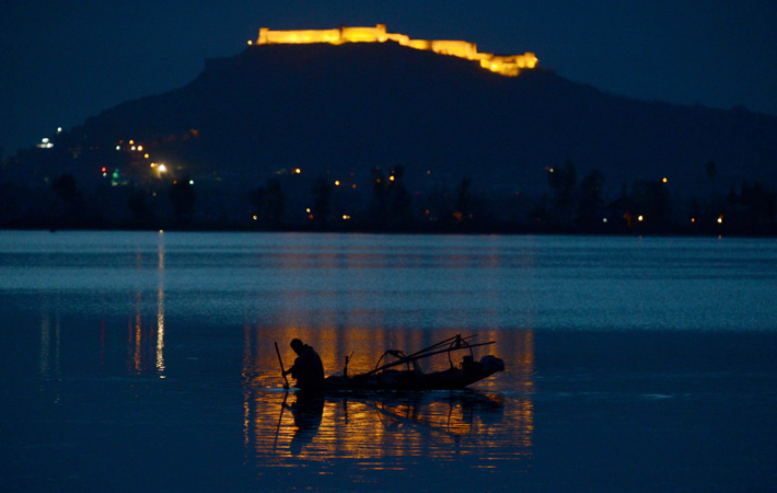 A Kashmiri Muslim fishes on Dal Lake in Srinagar on April 10, 2013. Tourists arrivals are picking up after a sharp fall in the wake of protests over the hanging of Kashmiri activist Afzal Guru in February, for an attack on India's parliament in 2001.