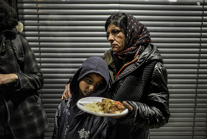 People of the Roma community who were evicted from their camp receive food before sleeping, in front of Lyon's administrative court, prior to a hearing regarding the ruling on their eventual rehousing.