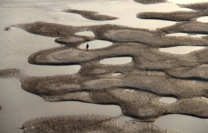 "This picture taken on April 9, 2013 shows a man walking along the riverbed of the Hanjiang River during its dry season in Shiyan, central China's Hubei province. China's coastal waters are suffering ""acute"" pollution, with the size of the worst affected areas soaring by more than 50 percent last year, an official body said."