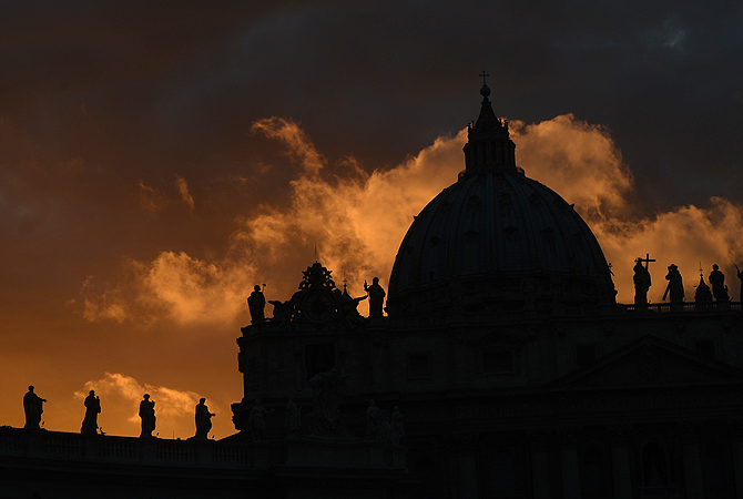 A picture shows the St Peter's basilica at sunset on the eve of the conclave at the Vatican. Catholic cardinals had a final day of jockeying for position the same day before shutting themselves into the Sistine Chapel to elect a new pope after Benedict XVI's shock resignation, with an Italian and a Brazilian who both head powerful archdioceses among the top contenders.