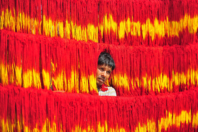An Indian artisan hangs freshly dyed kalawa thread, a traditional sacred orange-yellow thread used in Hindu rituals, for drying at Lalgopalgunj village, some 45 kilometers from Allahabad, April 10, 2013. Muslim artisans in the village are involved in the dyeing process of kalawa thread and chunri cloth.