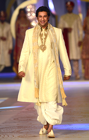 Pakistani cricket legend Wasim Akram presents a creation by Pakistani designer Deepak Perwani . — AFP Photo