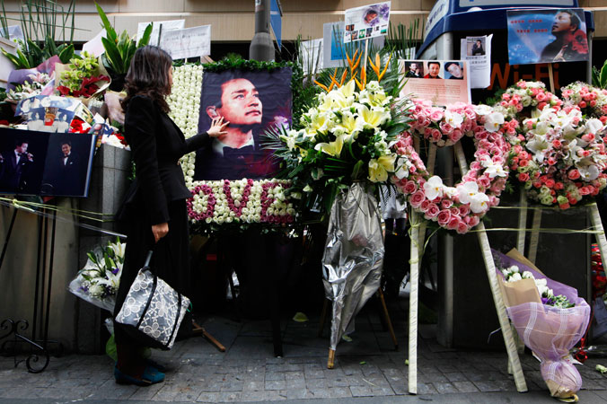 A fan touches a picture of Leslie Cheung on an altar set up outside a hotel where Cheung jumped to his death in Hong Kong.