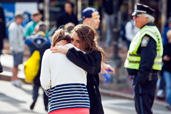 A woman comforts another, who appears to have suffered an injury to her hand.