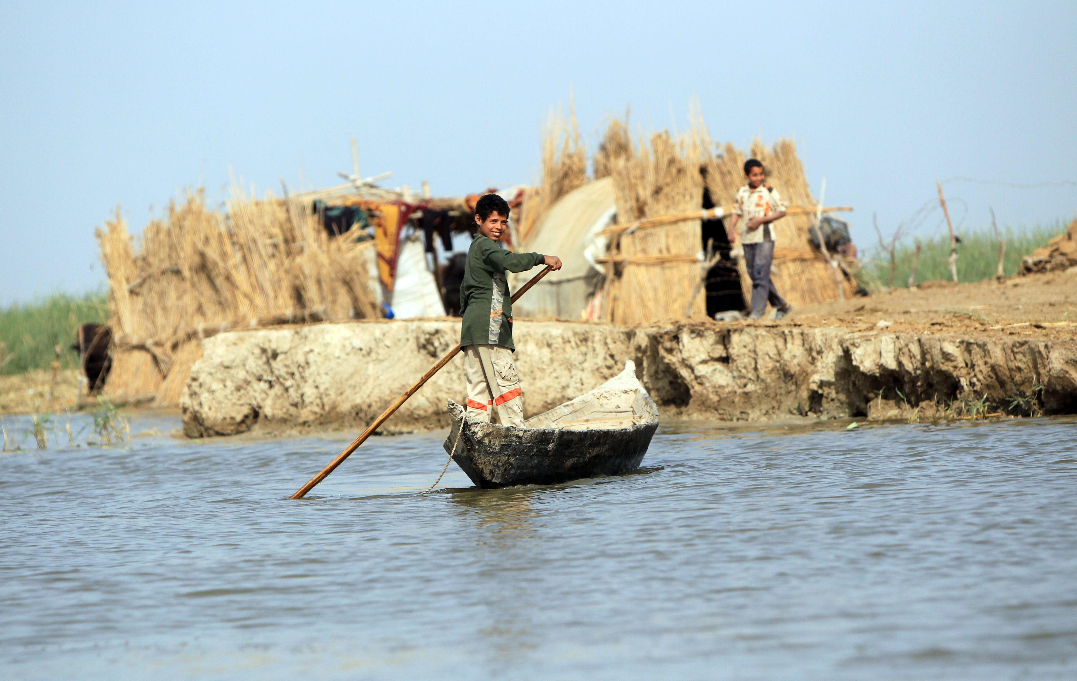 An Iraqi boy paddles a boat in the marshes near the small township of Chebayish, on the left bank of Euphrates, near Nasiriyah, 300 kilometres southeast of Baghdad, on April 6, 2013. The inhabitants of these ancient marshes are today suffering from the slow suffocation of the marshes due to drought which is altering their fishing patterns and the migration of birds and the breeding of water buffalo. During the regime of the late leader Saddam Hussein, sections of the marshes were drained.