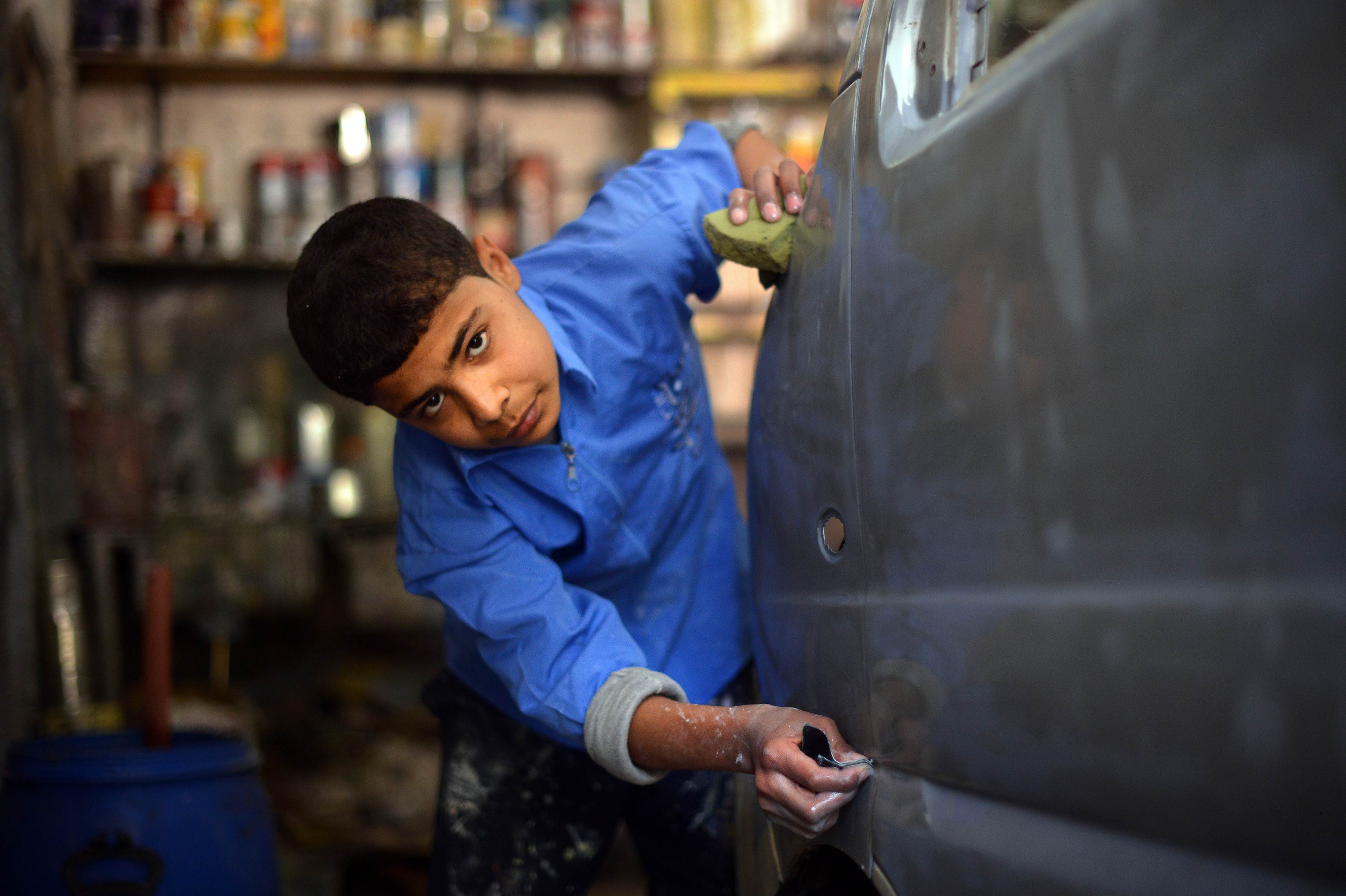 A Syrian boy works at a garage in the northern Syrian city of Aleppo on April 6, 2013. Conflict in neighbourhoods of Aleppo, which has been shaken by war for nine months, has put an end to childhood for most youths and it is not uncommon to see young boys working in the streets.