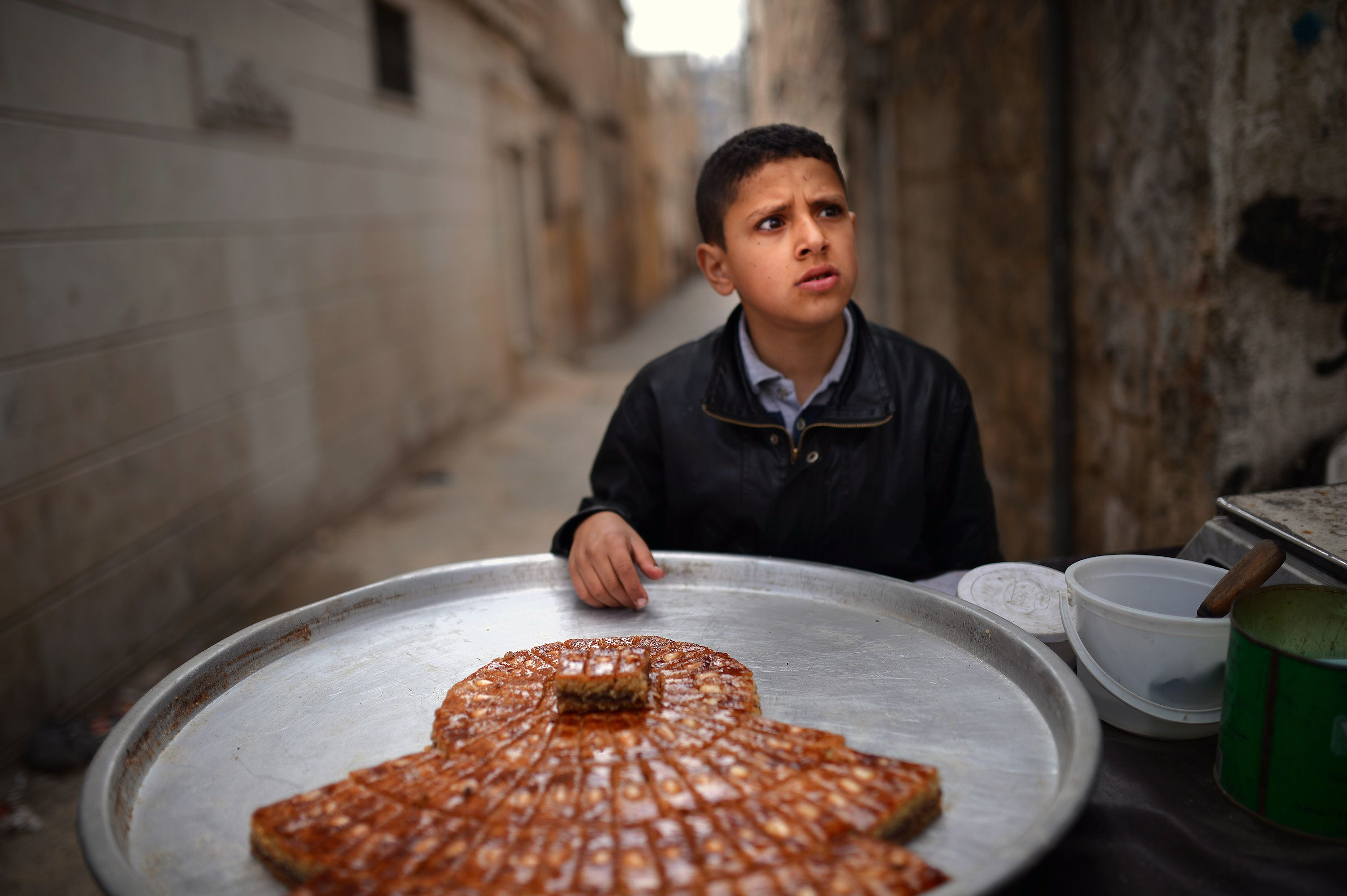 A Syrian boy sells sweets in the northern Syrian city of Aleppo on April 6, 2013. Conflict in neighbourhoods of Aleppo, which has been shaken by war for nine months, has put an end to childhood for most youths and it is not uncommon to see young boys working in the streets.