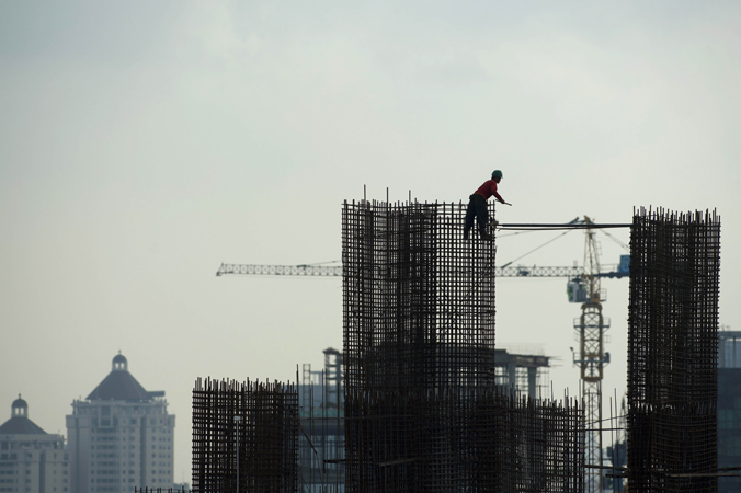 A construction worker builds iron reinforcement column at a high rise office building construction site in Indonesia's capital Jakarta. —Photo by AFP