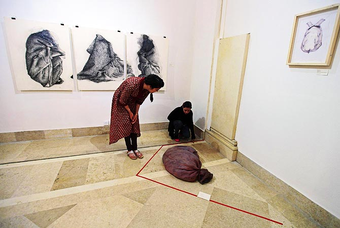 Visitors look at a latex russet-coloured sack designed to feel like human skin, at an exhibition.