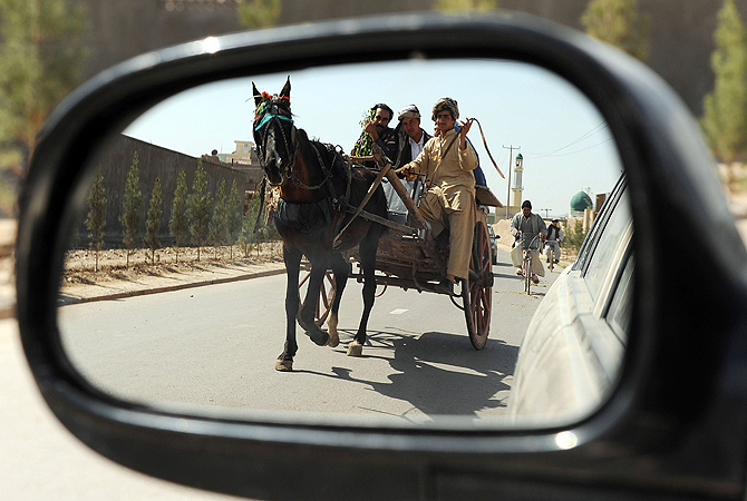 "Afghan villagers are reflected mirror as they ride in a traditional cart along a street in Heart. Some nine million Afghans or 36 per cent of the population are living in ""absolute poverty"" while another 37 per cent live barely above the poverty line, according to a UN report."