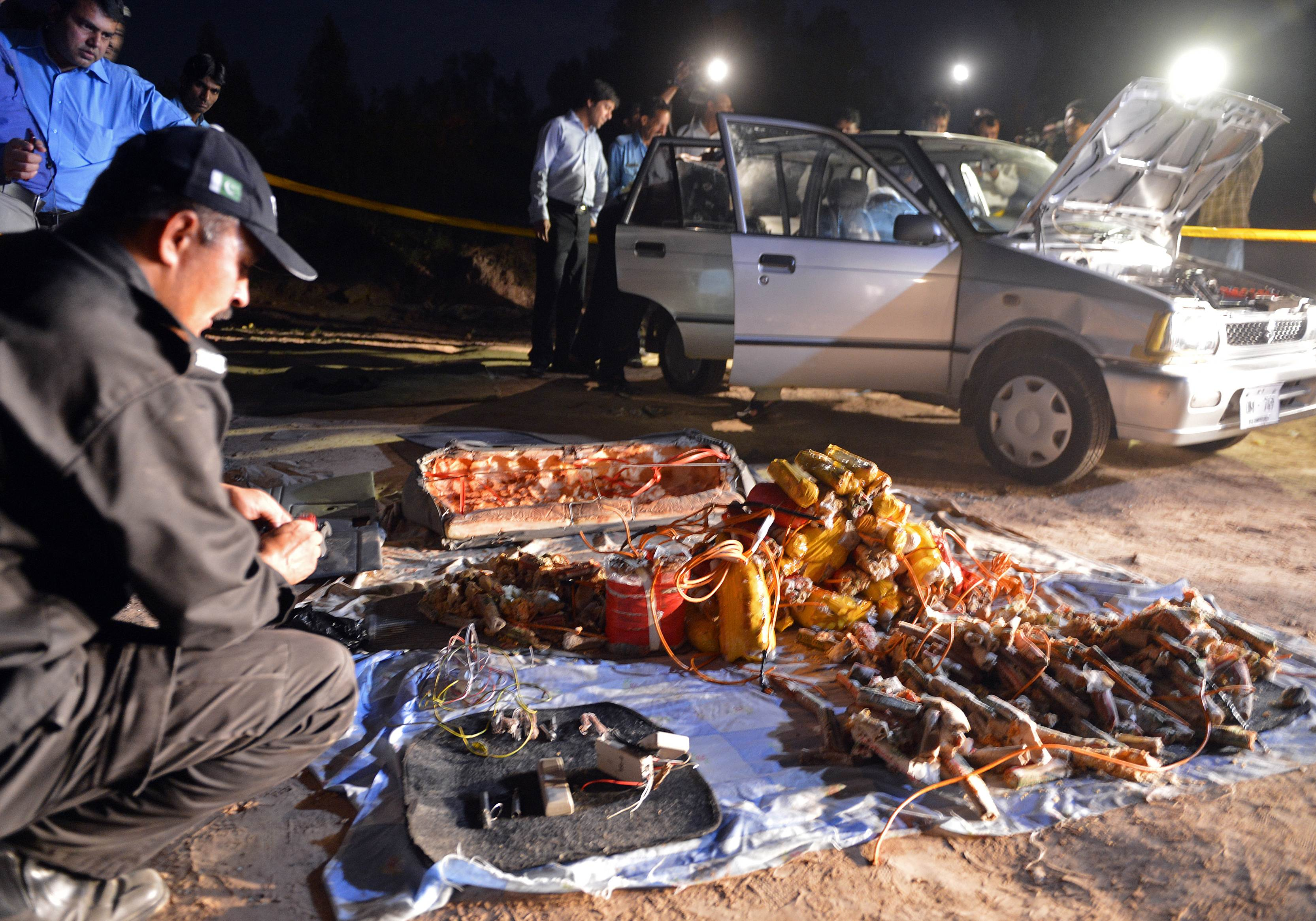 Pakistani security officials search a vehicle, found packed with explosives, after its seizure by police in the outskirts of Islamabad on April 23, 2013. The explosives-laden car was found parked on a roadside leading to the villa of former Pakistani military ruler Pervez Musharraf, where he is under house arrest. The Pakistani Taliban have threatened to assassinate the former military ruler who escaped three assassination attempts during his 1999-2008 rule who lost public support during his self exile. — AFP Photo
