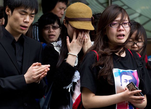 Fans of the late Hong Kong canto-pop star Leslie Cheung cry outside the Mandarin Oriental Hotel in Hong Kong.