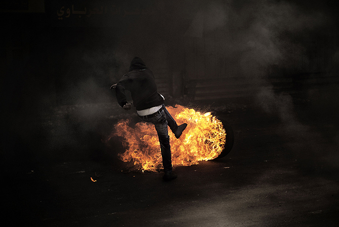 A Palestinian demonstrator kicks a flaming tire during clashes with the Israeli army in the West Bank city of Hebron on April 3, 2013. Palestinians across the West Bank and Gaza were observing a general strike, with prisoners refusing food to mourn the death of a fellow inmate in an Israeli jail.