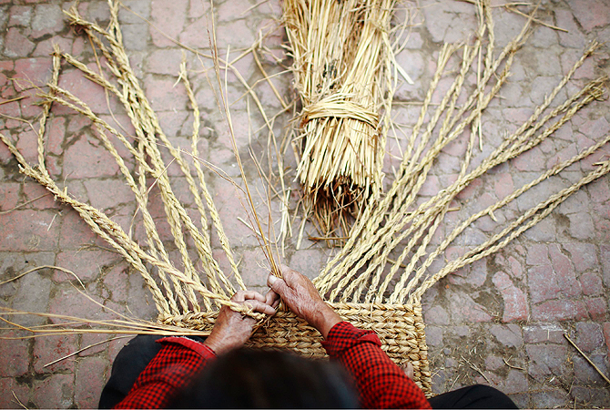 "A woman weaves a traditional carpet, also known as ""sukul"" in Nepali, using dried hay in Lalitpur."