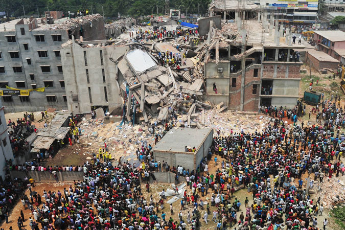Bangladeshi volunteers and rescue workers are pictured at the scene after an eight-storey building collapsed in Savar. —Photo by AFP