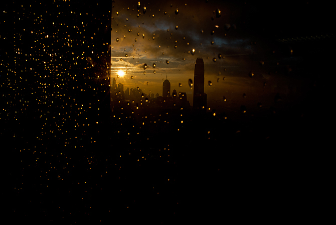 Rain drops on a window reflect the setting sun as it goes down above the central business district of Hong kong.  According to the Hong Kong observatory, a trough of low pressure is bringing unsettled weather to the coast of southern China.