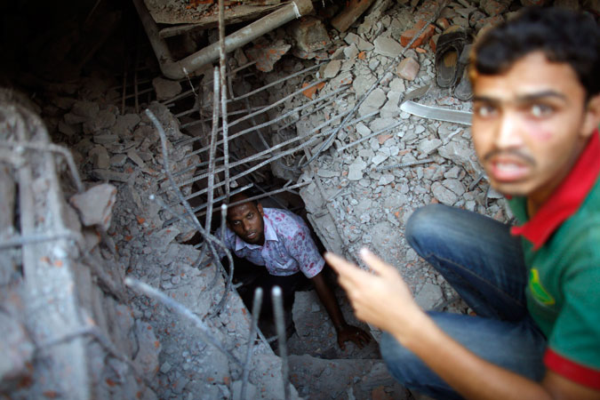 Rescue workers try to save trapped garment workers in the Rana Plaza building which collapsed. —Photo by Reuters