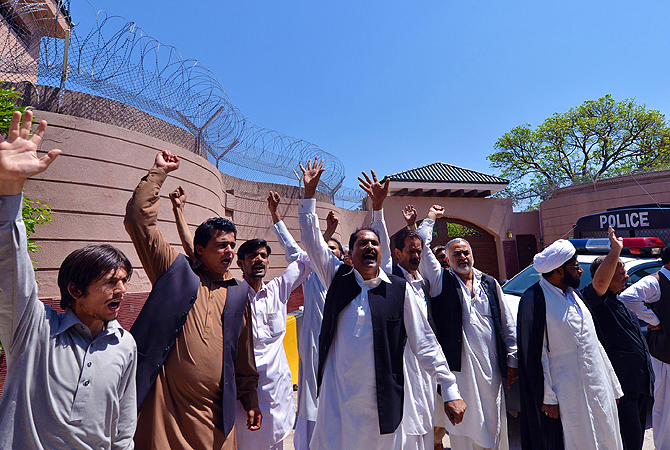 Supporters of former Pakistani president Pervez Musharraf shout slogans outside his residence after a court ordered for his arrest in Islamabad on April 18, 2013.