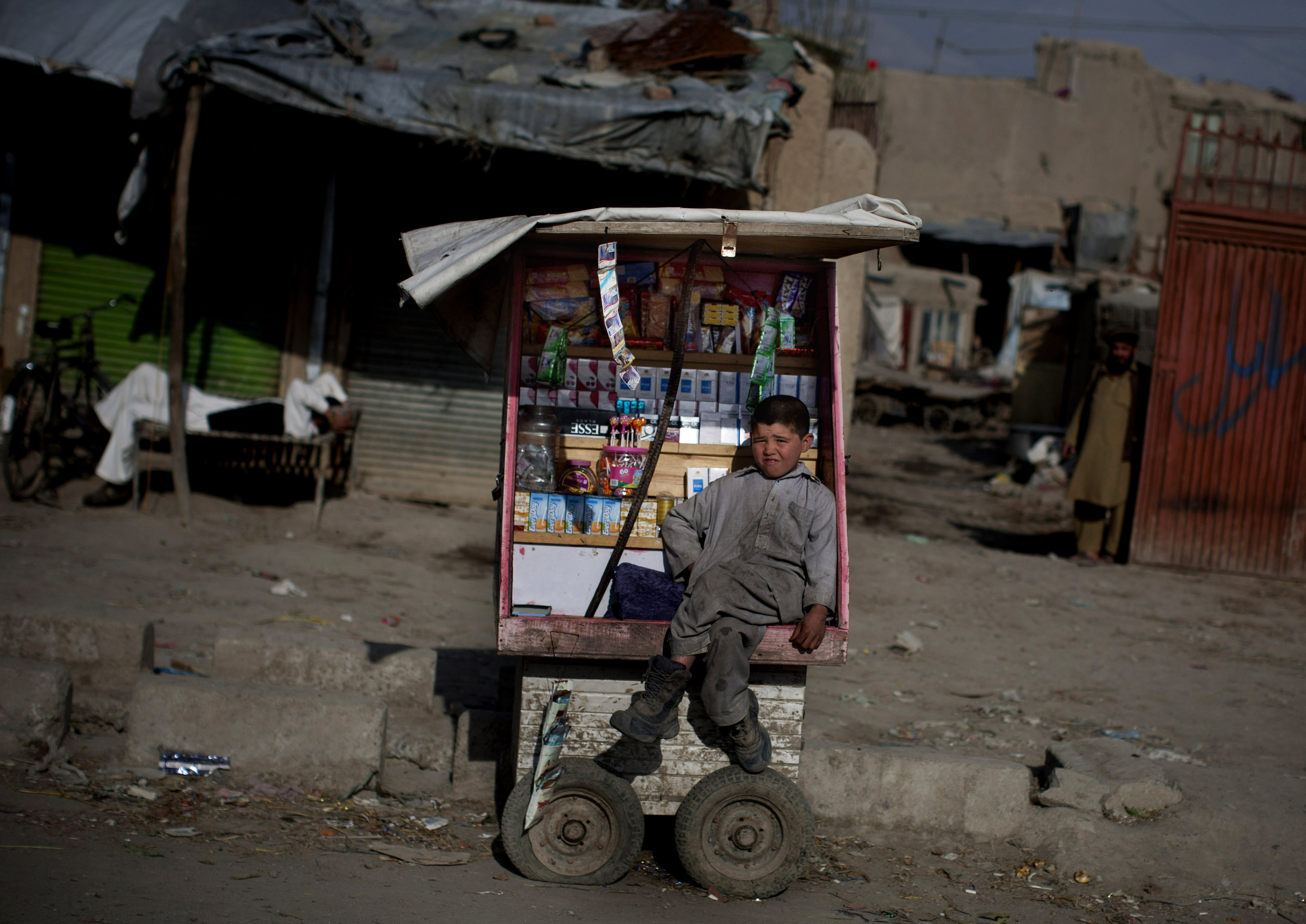 An Afghan boy sits on his cart as he waits for customers in the old town of Kabul, Afghanistan, Sunday, April 7, 2013.