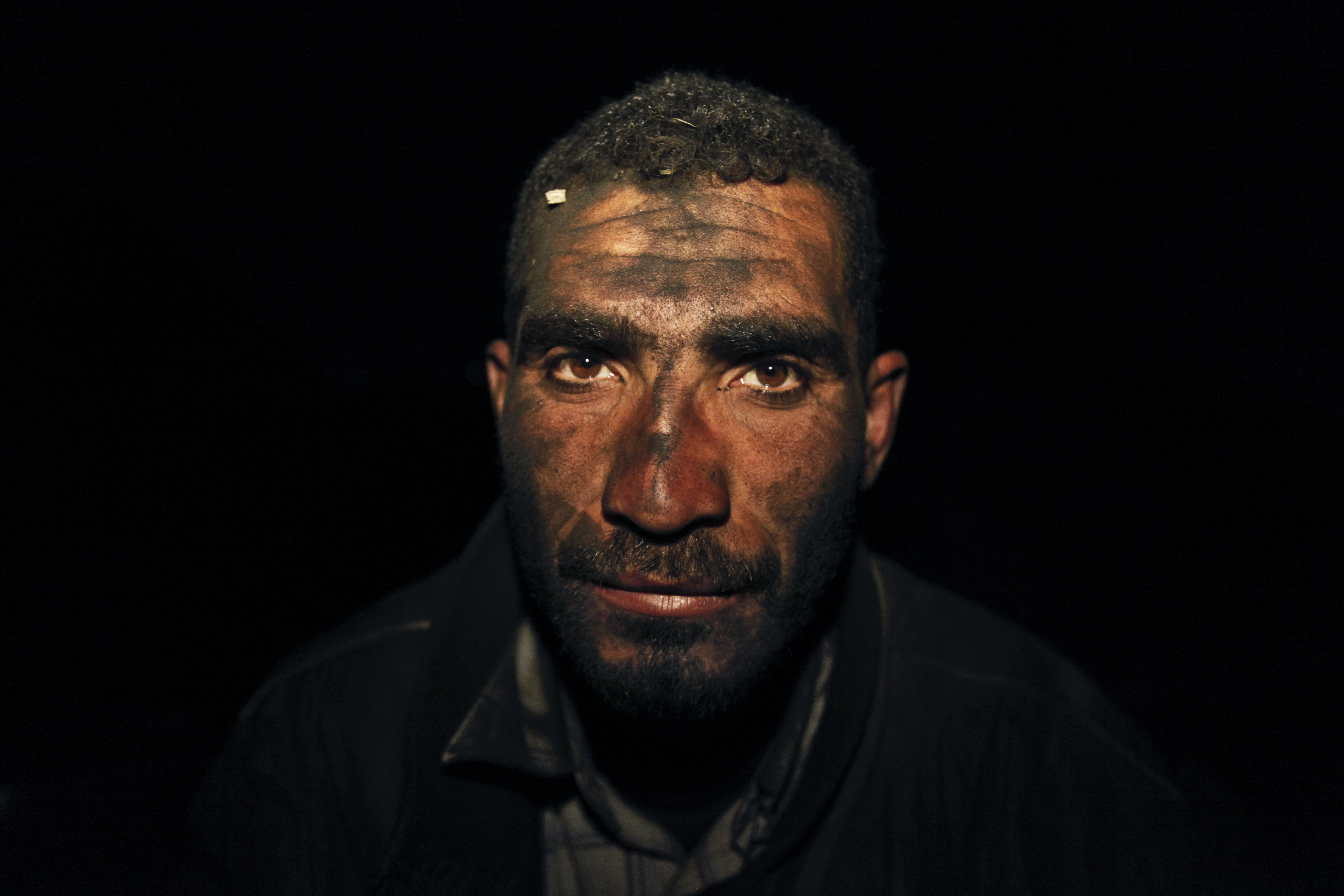 Palestinian worker Hamuda Mahdi, who oversees production of coal at night, poses for a photograph at one of the few local charcoal manufacturing shops, east of Gaza City.