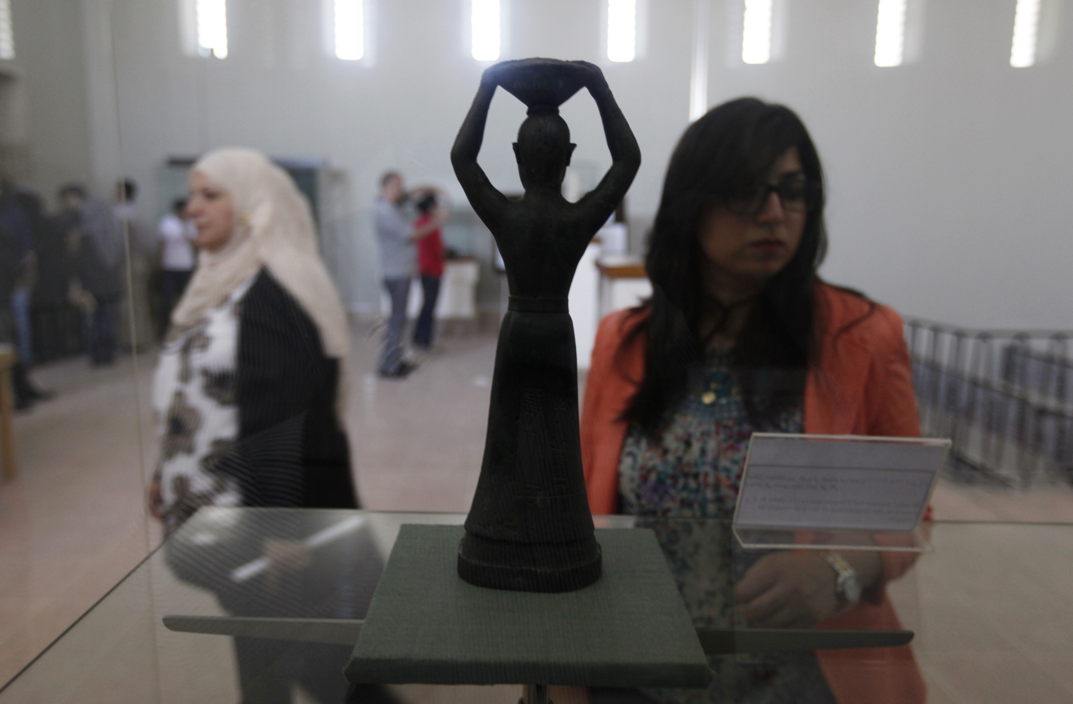 A woman looks at a statue of Ur-Nammu (2111 to 2094 BC)