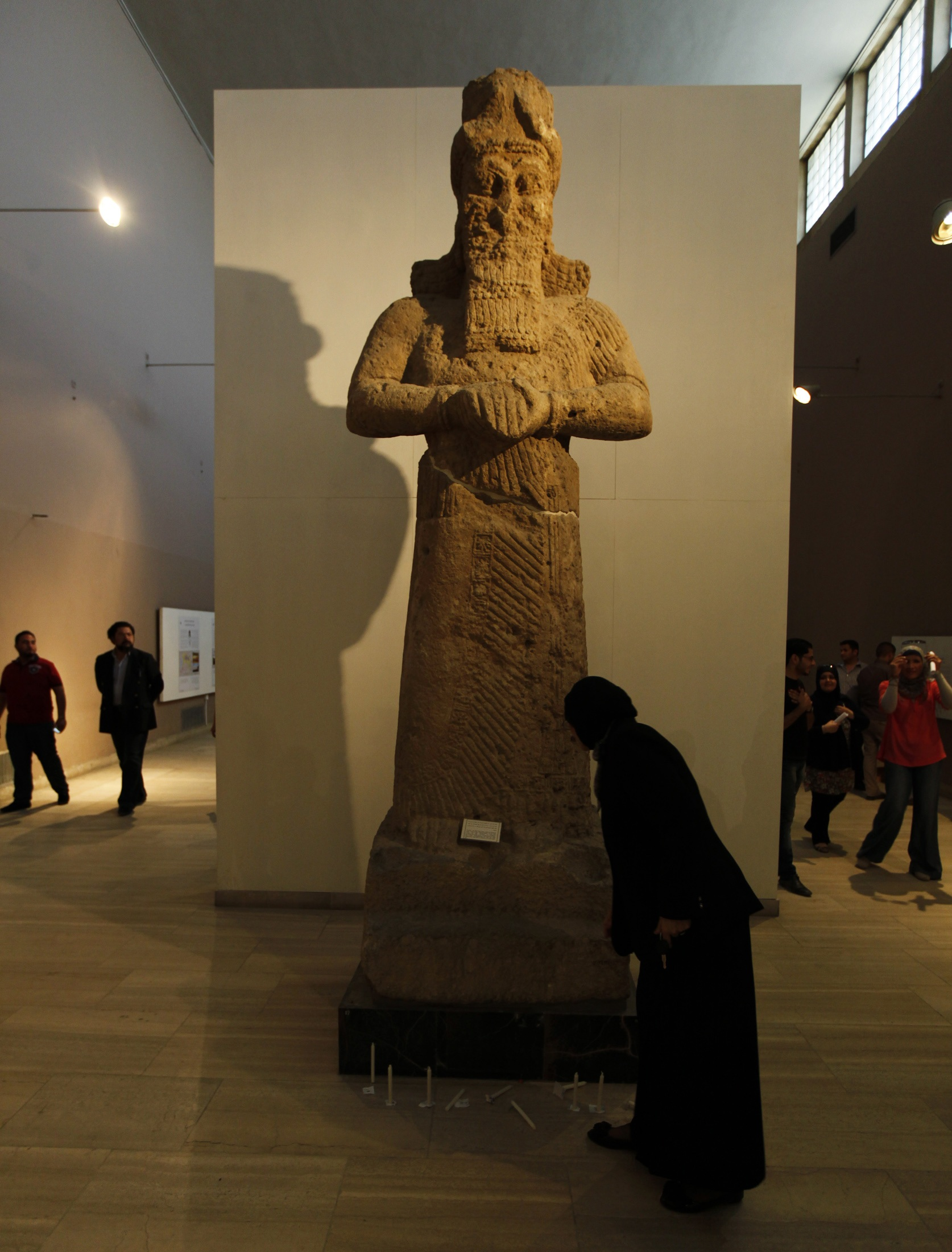 A woman stands next to an Assyrian statue inside the National Museum of Iraq in Baghdad.