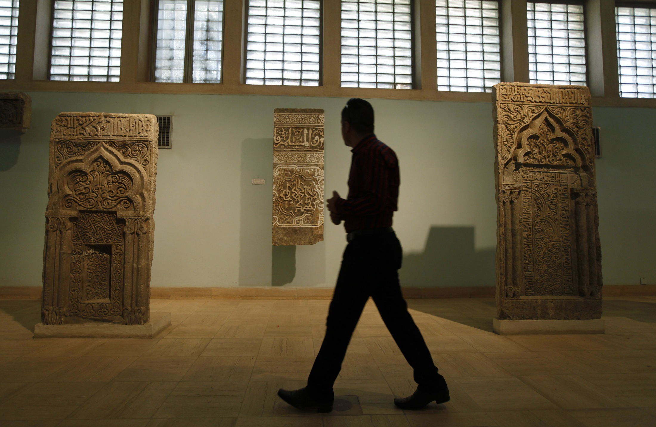 A man walks past artifacts inside the National Museum of Iraq in Baghdad.