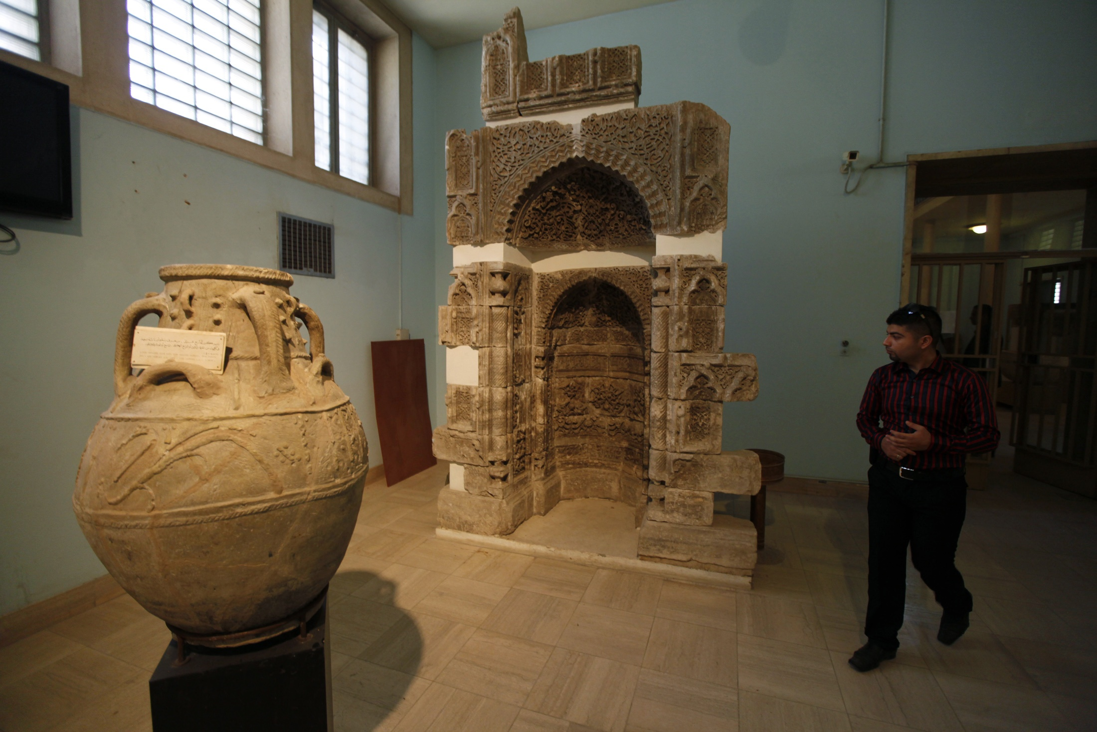 A man walks past artifacts at the National Museum of Iraq in Baghdad.