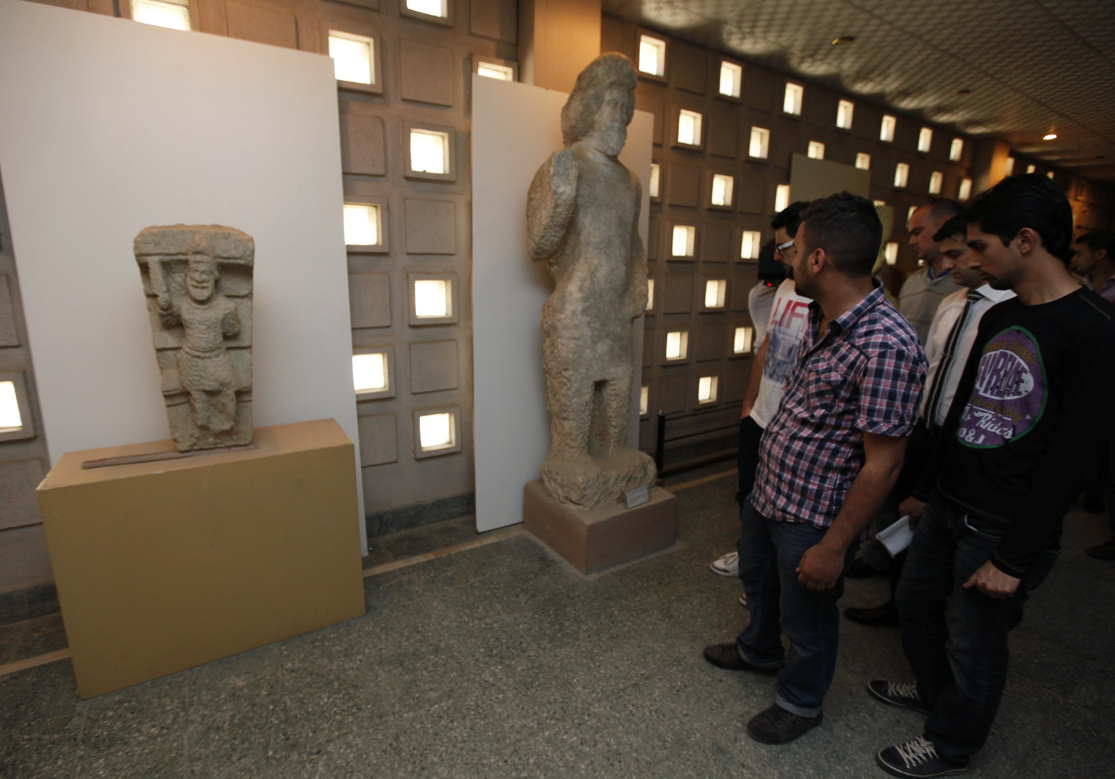 People look at a limestone statue, dating back to the second and third century AD.