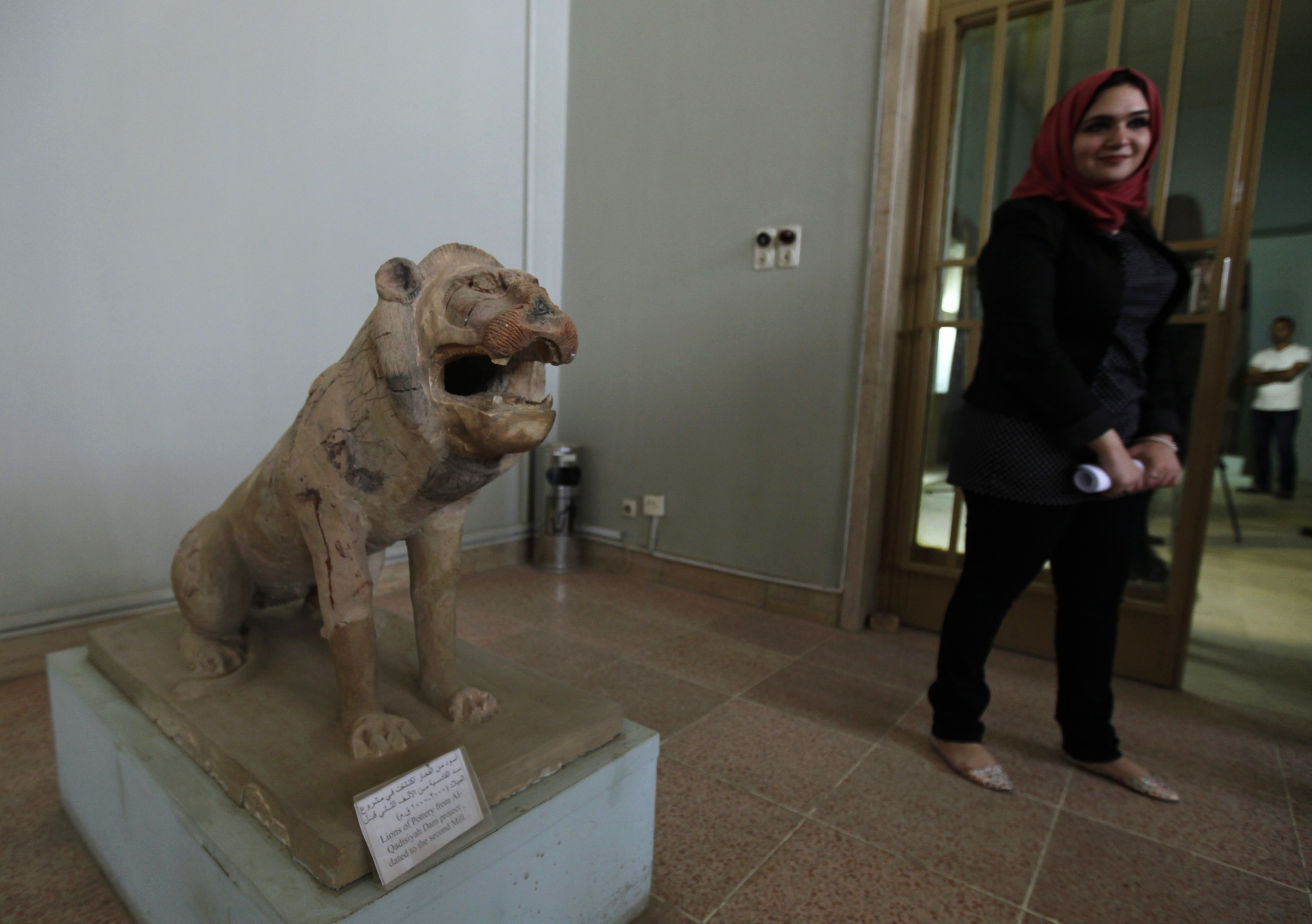 A woman walks past a statue of a lion, which dates back to the Assyrian period in the second millennium BC