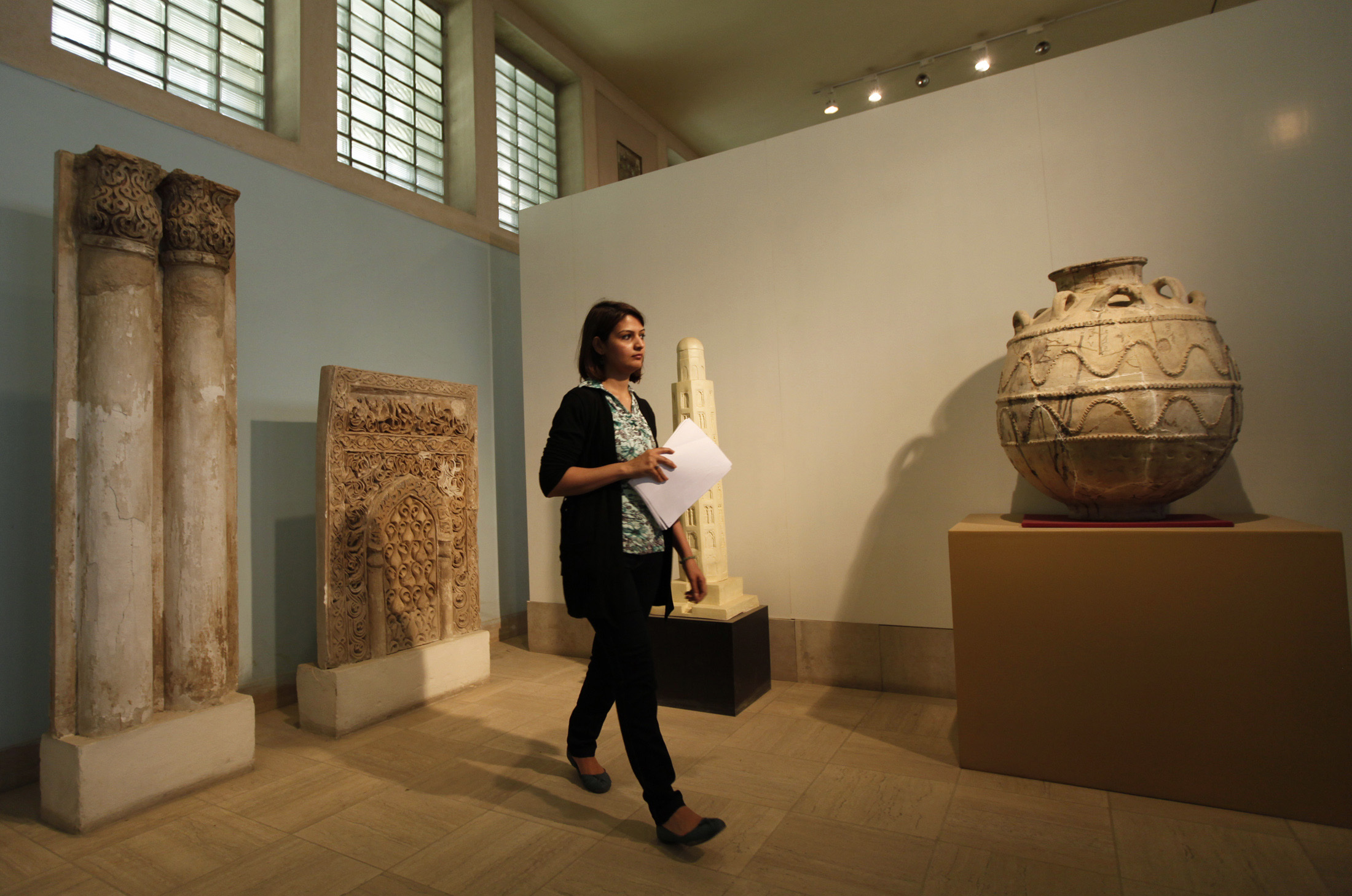 A woman walks past artifacts at the National Museum of Iraq in Baghdad April 8, 2013.
